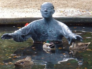 Photo of blind-folded statue in a pond, with ducks swimming just beyond the figure's hands