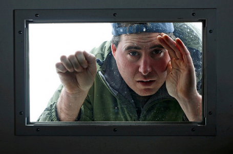 Photo of guy peering into window, knocking as if he's timidly asking to be let into the warmth.