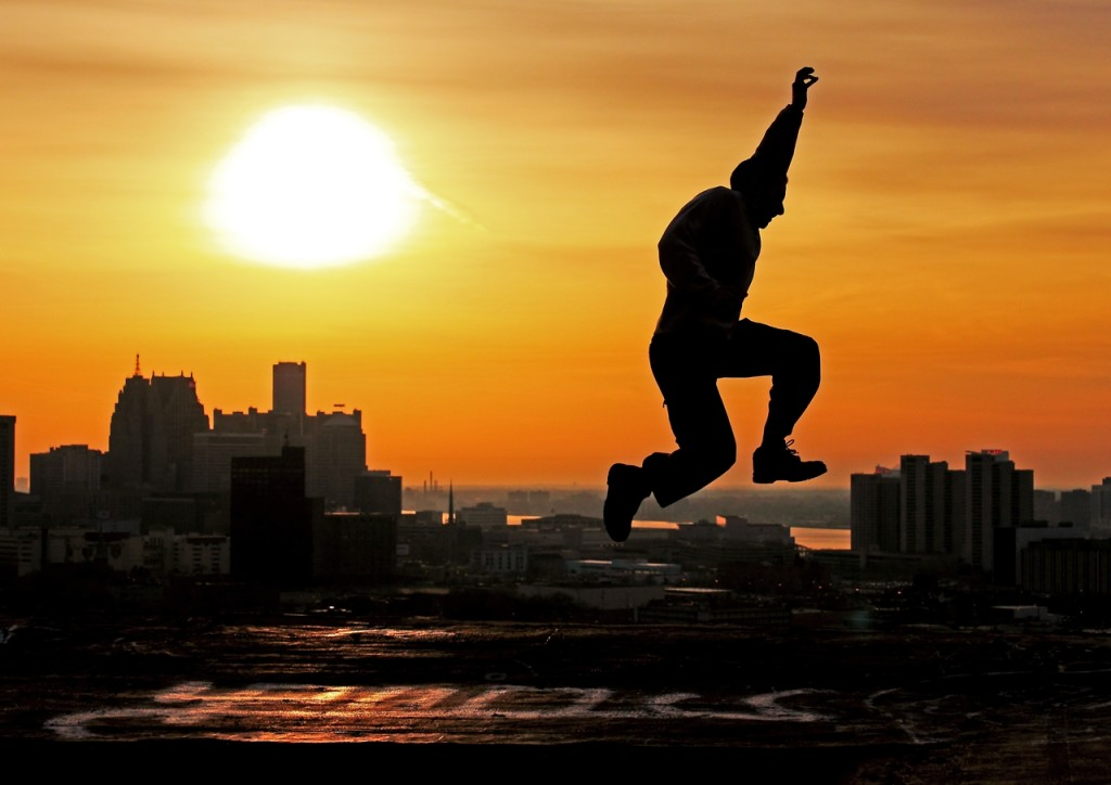 silhouette of man leaping with city skyline in background.